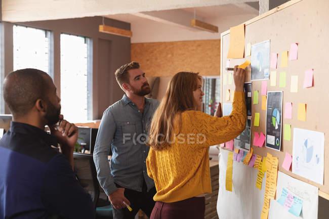 Вид сбоку на молодого афроамериканца и молодого кавказца, стоящего и смотрящего, как их молодая кавказская коллега пишет на доске идей во время группового мозгового штурма в творческом офисе — стоковое фото