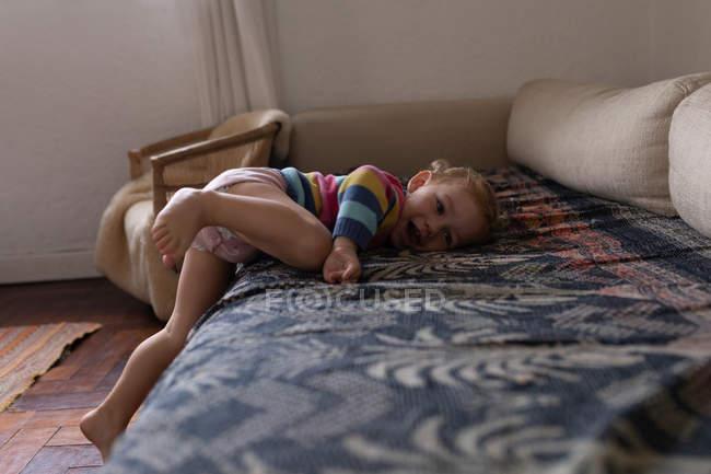 Вид сбоку на белого ребенка, лежащего на диване и улыбающегося босиком — стоковое фото