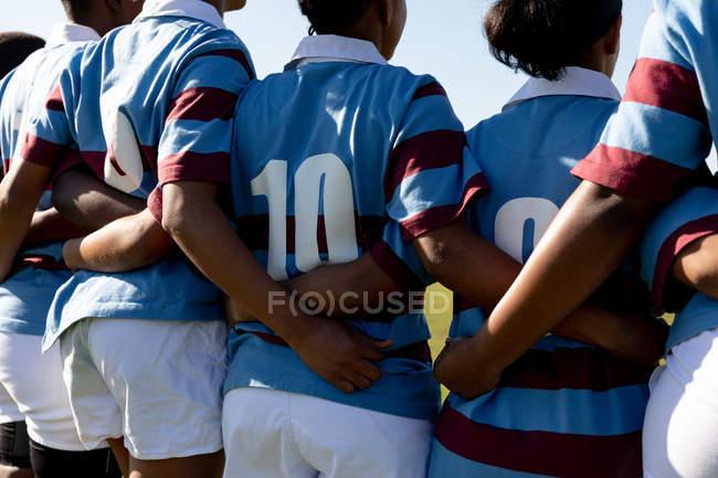 Rückansicht Mittelteil einer Mannschaft von Rugbyspielerinnen, die mit verbundenen Armen auf einem Rugbyfeld stehen und sich auf ein Rugbyspiel vorbereiten — Stockfoto