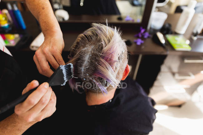 Погляд зблизька середнього віку Кавказький самець перукаря і молода кавказька жінка з розфарбованим волоссям в салоні для волосся. — стокове фото