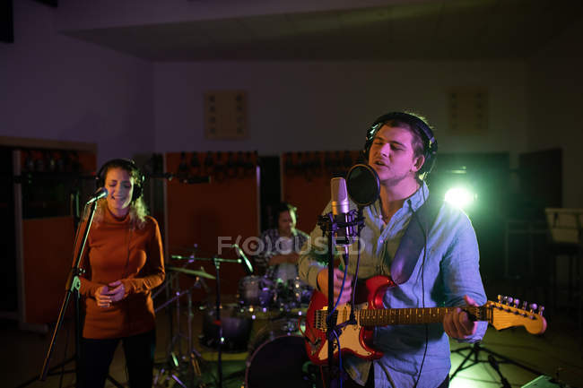 Front view of a young Caucasian female singer, a young Caucasian male singer guitarist and drummer performing during a session at a recording studio — Stock Photo