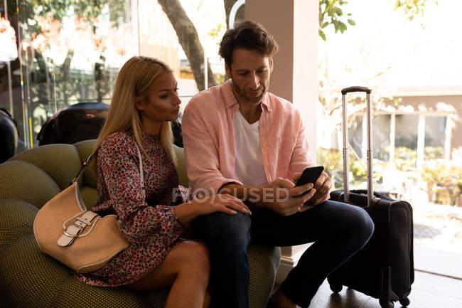 Вид на счастливую молодую кавказскую пару, отдыхающую на отдыхе, сидящую с чемоданом за пределами отеля, с помощью смартфона — стоковое фото