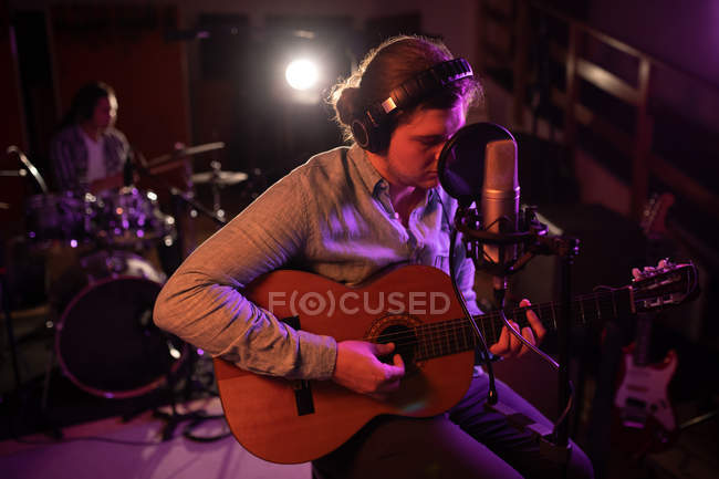 Front view close up of a young Caucasian man wearing headphones sitting and playing an acoustic guitar in front of a microphone during a session at a recording studio, with a drummer sitting behind a drum kit in the background — Stock Photo