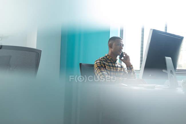 Вид сбоку на молодого афроамериканца, сидящего за столом за компьютером и разговаривающего на смартфоне в современном офисе креативного бизнеса, с размытым передним план — стоковое фото