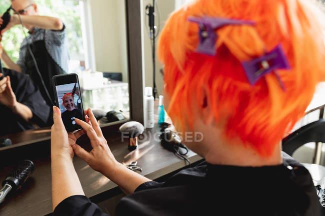 Обличчя заднього виду близько середнього віку Кавказький самець перукаря і молода кавказька жінка, які роблять вибір, маючи яскраво-червоне волосся в салоні для волосся, відображені в дзеркалі. — стокове фото