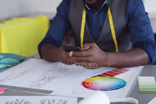 Vista frontal de la sección central del estudiante de moda masculino usando un teléfono inteligente mientras trabaja en un diseño en un estudio en la universidad de moda - foto de stock