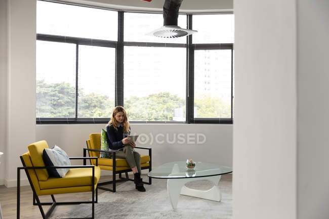 Front view of a young Caucasian woman sitting in an armchair using a tablet computer in the lounge area of a creative business — Stock Photo