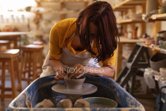 Frontansicht einer jungen kaukasischen Töpferin, die an einer Töpferscheibe sitzt und in einem Töpferatelier mit ihren Händen Ton formt — Stockfoto