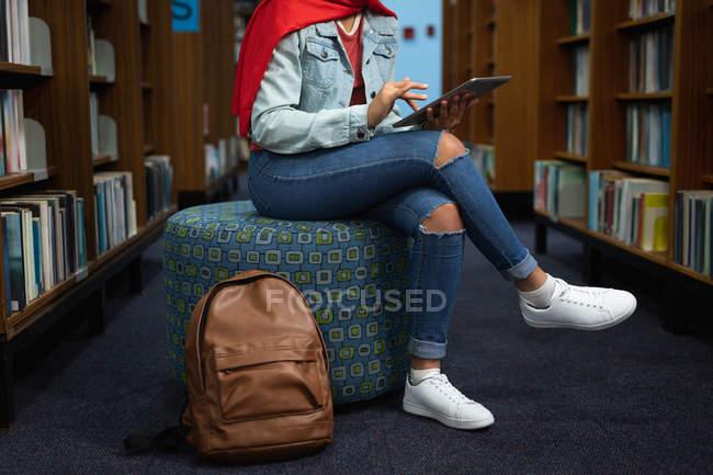 Vista laterale bassa sezione di studentessa che usa un tablet e studia in una biblioteca — Foto stock