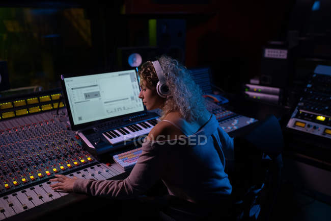 Side view close up of a young Caucasian female sound engineer sitting and working at a mixing desk in a recording studio wearing headphones — Stock Photo