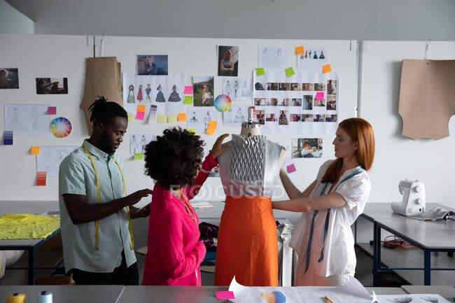 Seitenansicht eines jungen afrikanisch-amerikanischen Mannes, einer kaukasischen Frau und einer gemischten Rasse Modestudentinnen, die in einem Atelier der Modehochschule an der Gestaltung von Kleidungsstücken an einer Schaufensterpuppe arbeiten — Stockfoto