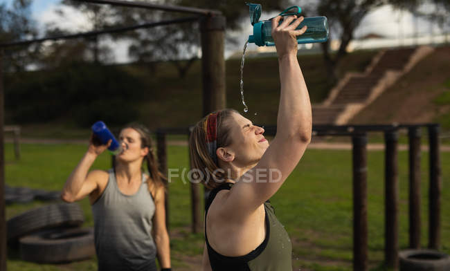 Side view of a young Caucasian woman pouring water from a bottle over her head to cool down at an outdoor gym during a bootcamp training session, another woman is drinking water in the background — Stock Photo
