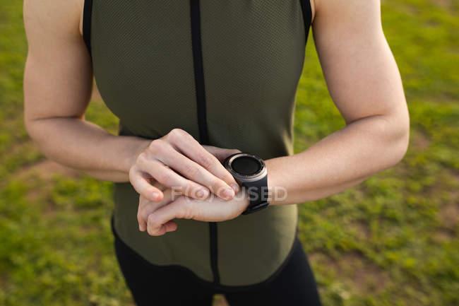 Вид спереди на среднюю часть женщины, стоящей и проверяющей свои часы в открытом тренажерном зале во время тренировки в буткемпе — стоковое фото