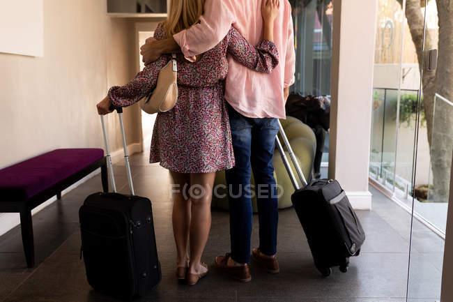 Vista trasera sección baja de la pareja que se relaja en vacaciones llegando con maletas a un hotel, abrazando - foto de stock