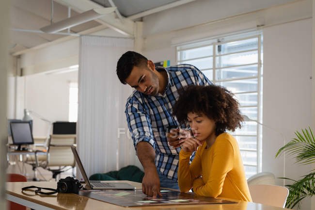 Side view of a young mixed race man standing and a young mixed race woman sitting at a desk having a discussion at a creative office — Stock Photo