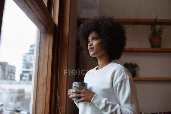 Vista laterale da vicino di una giovane donna di razza mista in piedi vicino a una finestra a casa guardando fuori, con in mano una tazza di caffè — Foto stock