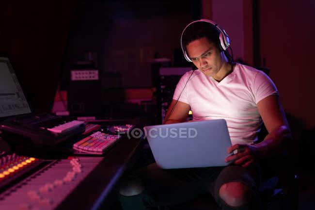 Фронт-вью крупным планом молодого инженера смешанной расы, сидящего и работающего за микширующим столом в студии звукозаписи с помощью ноутбука и в наушниках — стоковое фото