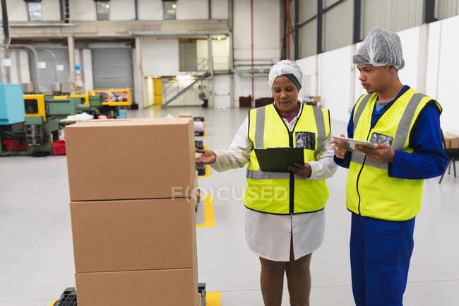 Vista frontale da vicino di una giovane donna di razza mista e di un giovane operaio di una fabbrica di razza mista che parla in un magazzino di carico in una fabbrica . — Foto stock