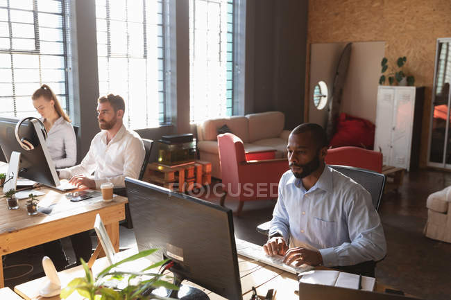Front view of a young African American man and a young Caucasian woman and man sitting at desks using computers in a creative office — Stock Photo
