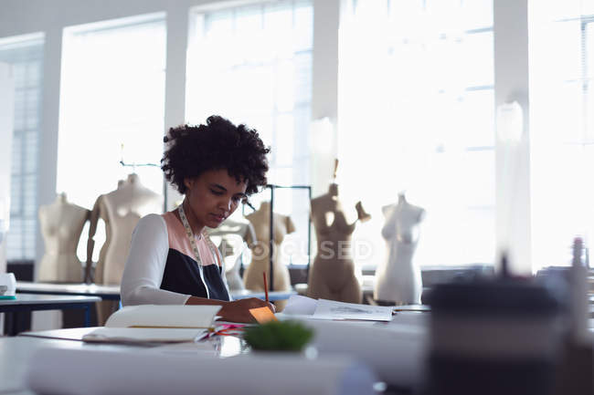 Front view of a young mixed race female fashion student sitting at a table working on a design in a studio at fashion college — Stock Photo
