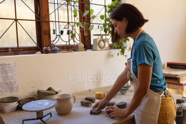 Side view of a young Caucasian female potter wearing an apron working with pieces of clay at a work table in front of a window in a pottery studio — Stock Photo