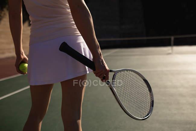 Задний план женщины, играющей в теннис в солнечный день, держащей ракетку и мяч — стоковое фото