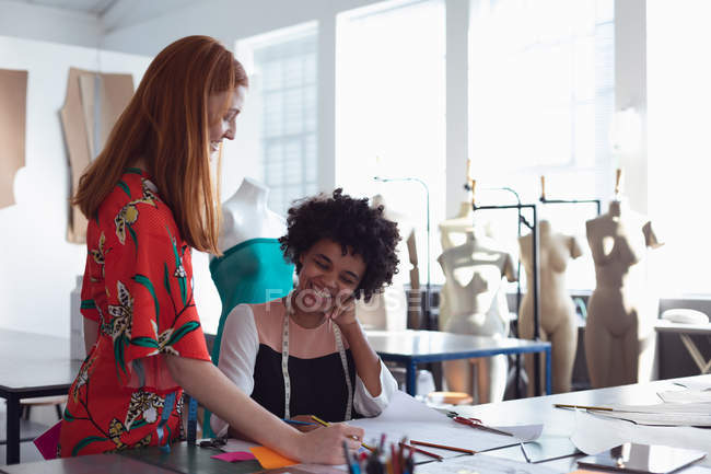 Front view of a young mixed race female fashion student sitting at a desk working on a design and talking to a young Caucasian female colleague standing beside her in a studio at fashion college with mannequins in the background — Stock Photo
