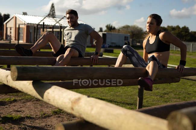 Vista frontal de una joven mujer caucásica y un joven caucásico trepando a través de vigas en un marco de escalada en un gimnasio al aire libre durante una sesión de entrenamiento de bootcamp - foto de stock