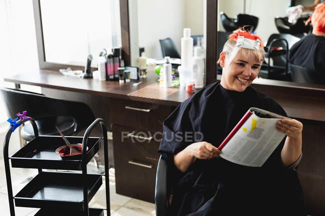 Vista frontale di una giovane cliente donna caucasica con i capelli colorati di rosso vivo in un salone di parrucchiere — Foto stock