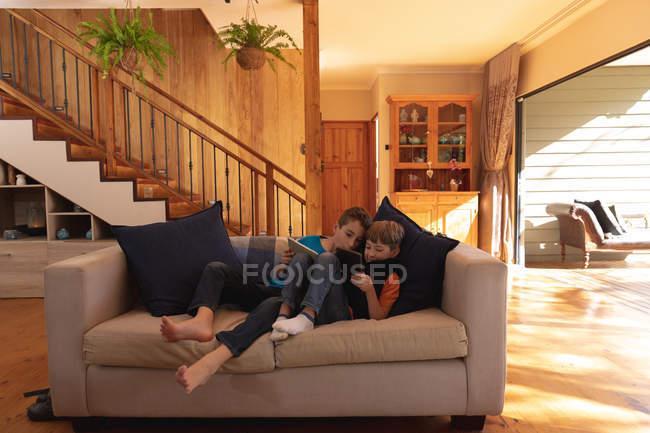 Вид спереди на двух белых мальчиков, лежащих на диване и использующих планшетные компьютеры в гостиной — стоковое фото