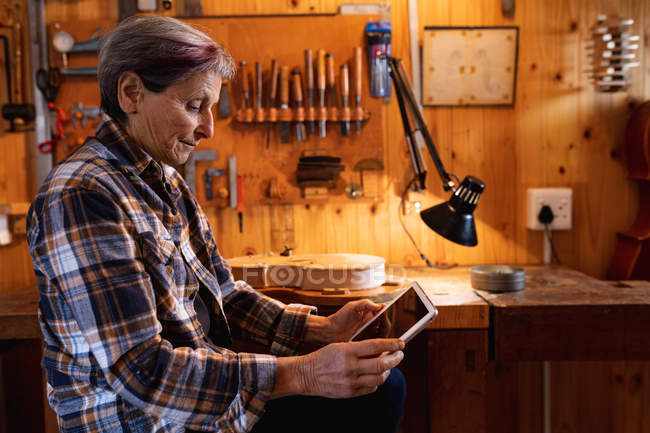 Side view of a senior Caucasian female luthier using a tablet computer with tools hanging up on the wall in the background — Stock Photo
