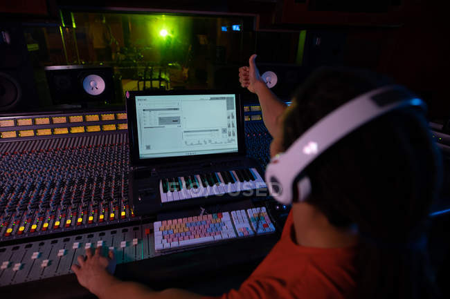 Over the shoulder view of a young mixed race male sound engineer sitting and working at a mixing desk in a recording studio using a computer and wearing headphones and giving a thumbs up sign during a recording session — Stock Photo