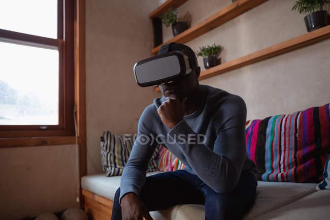 Vue de face gros plan d'un jeune Afro-Américain portant un casque VR assis sur un canapé à la maison, le menton posé sur sa main — Photo de stock