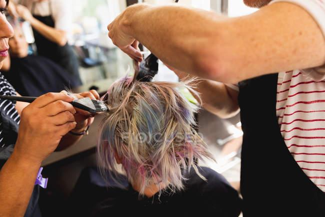 Visão traseira close-up de um cabeleireiro masculino caucasiano de meia-idade, uma cabeleireira mista de meia-idade e uma jovem mulher caucasiana com o cabelo colorido em um salão de cabeleireiro — Fotografia de Stock