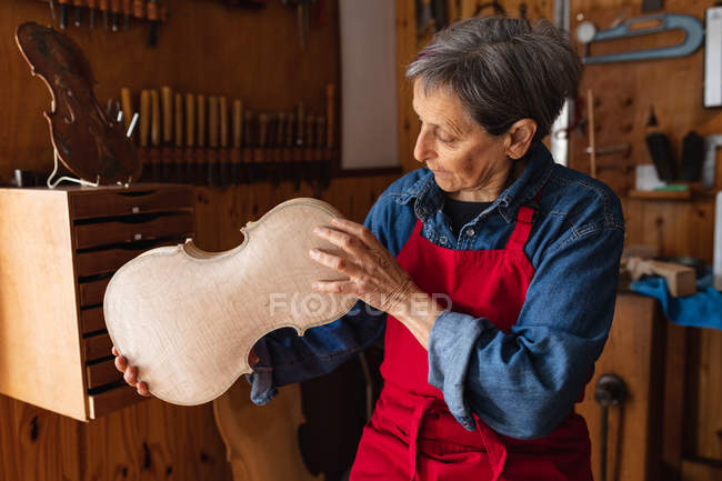 Вид спереди на старшую кавказку-лютирку, держащую тело скрипки в мастерской, с инструментами, висящими на стене на заднем плане — стоковое фото