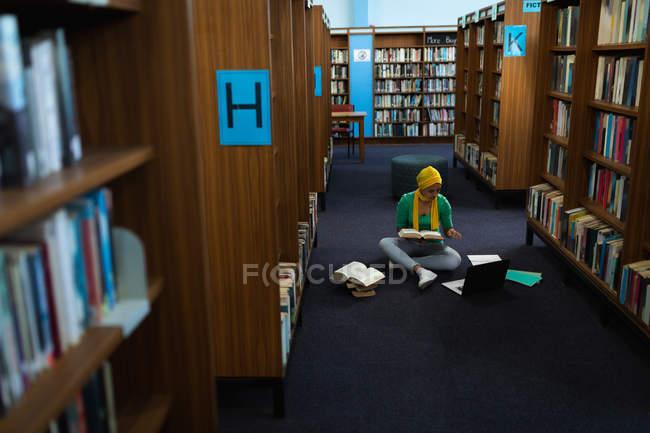 Vista frontale di una giovane studentessa asiatica che indossa un turbante con in mano un libro, usa un computer portatile e studia in una biblioteca — Foto stock