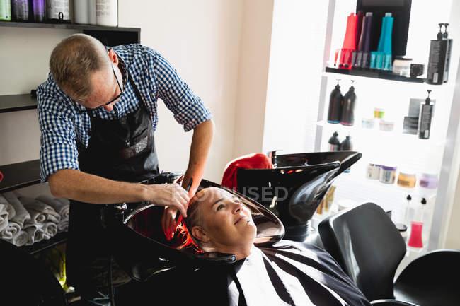 Vista frontale di un parrucchiere caucasico di mezza età e di una giovane donna caucasica che si lava i capelli in un parrucchiere — Foto stock