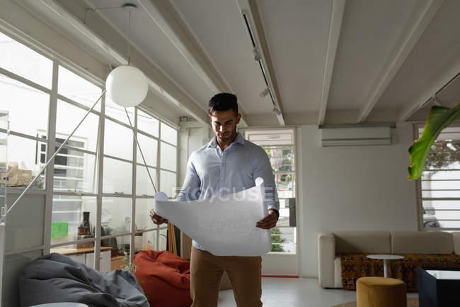 Vista frontal de un joven hombre de raza mixta de pie y comprobar los dibujos arquitectónicos en una oficina creativa. - foto de stock