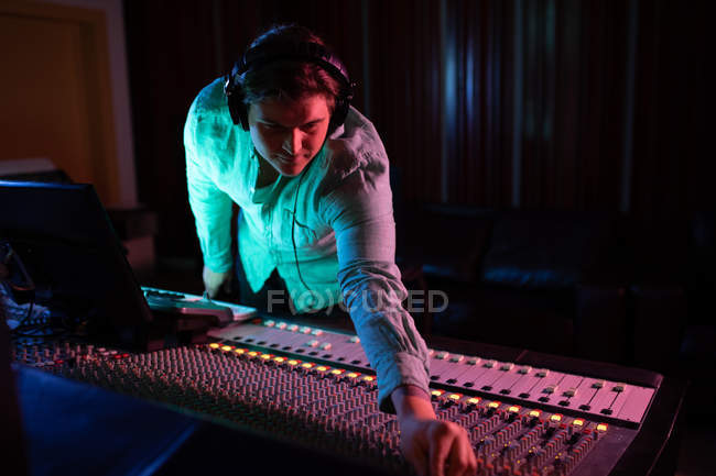 Front view close up of a young Caucasian male sound engineer wearing headphones reaching across a mixing desk in a recording studio to adjust a channel setting — Stock Photo