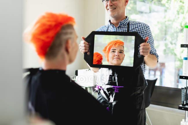 Передня картина середнього віку Кавказька перукарка і молода кавказька жінка з яскраво-червоним волоссям, показані в ручному дзеркалі в перукарні. — стокове фото