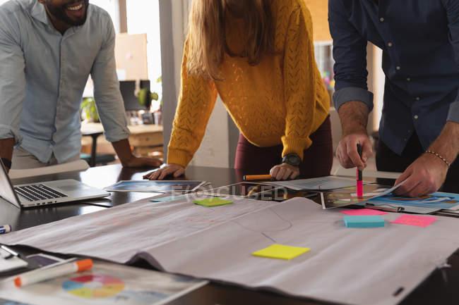 Vista lateral sección central de un joven afroamericano y un joven caucásico hombre y mujer inclinados sobre un escritorio trabajando juntos en un proyecto en una oficina creativa - foto de stock