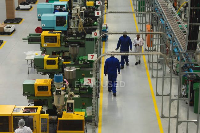 High angle view of factory workers interacting and walking past rows of machines in a warehouse at a factory processing plant — Stock Photo