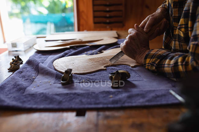 Close up side view of luthier working on the body of a violin on a workbench in her workshop — Stock Photo