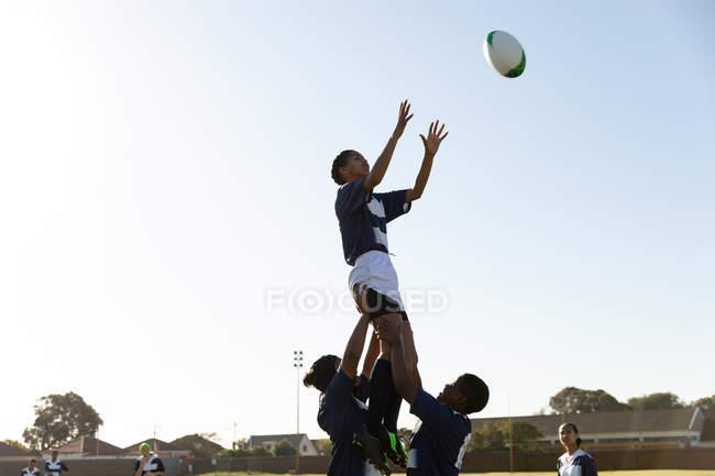 Vista laterale di un giovane giocatore di rugby femminile di razza mista adulto sollevato da due compagni di squadra per prendere la palla durante una partita di rugby — Foto stock