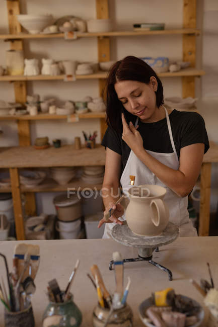 Front view a smiling young Caucasian female potter on the phone while glazing a jug in a pottery studio — Stock Photo