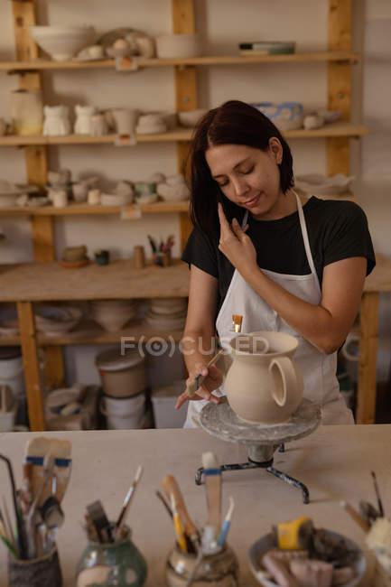 Vista frontal uma jovem oleiro caucasiano sorridente no telefone enquanto vidros um jarro em um estúdio de cerâmica — Fotografia de Stock