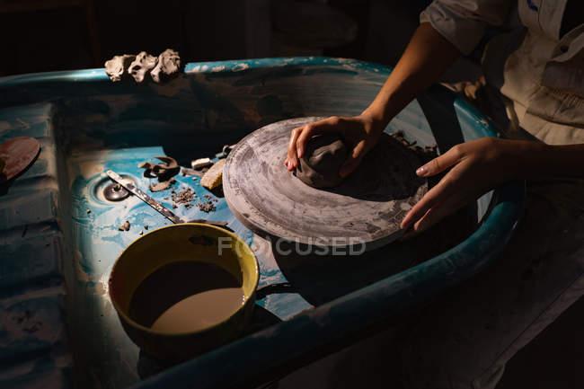 Seitenansicht Mittelteil einer Töpferin, die Ton formt, mit ihren Händen auf einer Töpferscheibe in einem Töpferatelier — Stockfoto
