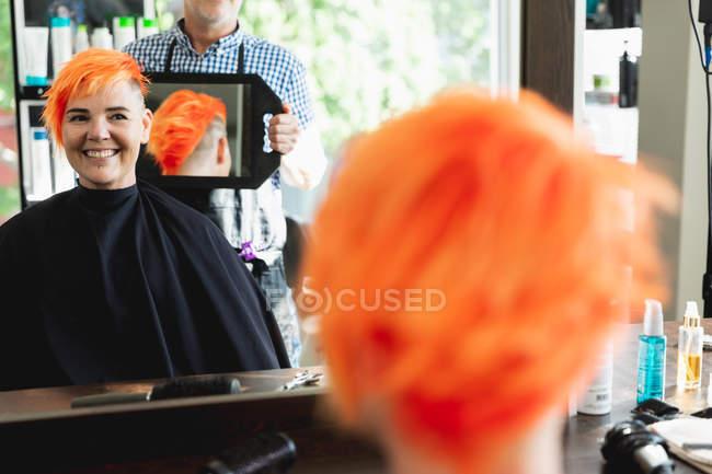 Обличчя заднього виду близько до середнього віку Кавказький самець перукаря і молода кавказька жінка з яскраво-червоним волоссям і показане в ручному дзеркалі в салоні для волосся. — стокове фото