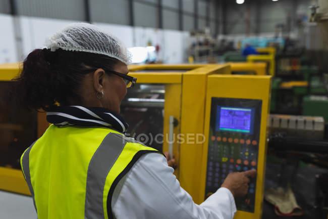 Вид сзади на Кавказскую женщину средних лет, работающую в очках и рабочей одежде на заводе — стоковое фото