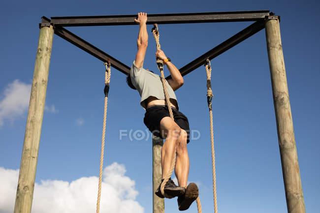 Vue avant d'un jeune homme caucasien escaladant une corde sur un cadre d'escalade à une gymnastique extérieure pendant une session de formation de bootcamp — Photo de stock